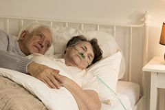 Man and his ill wife. Senior men holding his terminally ill wife in his arms, comforting her royalty free stock images