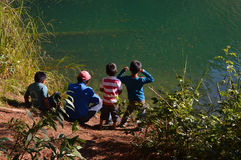 Man and his kids sitting by the laguna Esmeralda in Chiapas. Mexico royalty free stock photo