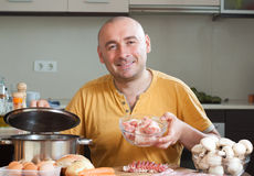 Man in  his kitchen with meat Stock Photography
