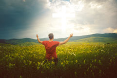 Man in his knees with hands up to the cross. Man sits in a meadow looking at a cross of light like a miracle royalty free stock photo