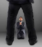 Man on his knees praying not to be dismissed Stock Photography