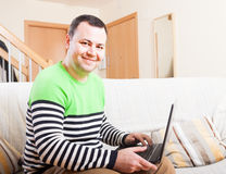 Man at his laptop. Adult man sitting at his laptop at home royalty free stock photography