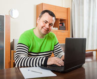 Man at his laptop at home. Man sitting at work on laptop at home royalty free stock photo