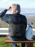 Man and his little dog. Elderly man and his little dog sitting on the bench looking at the ocean Royalty Free Stock Images