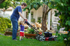 Man and his little son having fun with lawn mower in garden Royalty Free Stock Image