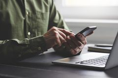 A man with his mobile phone in the office. A man using mobile phone in the office stock images