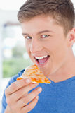 A man with his mouth open about to eat pizza. And looking at the camera Royalty Free Stock Photography
