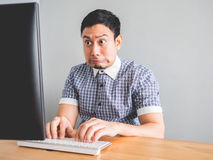 Man at his office desk. Asian man makes funny guilty face as he made a mistake in his work Royalty Free Stock Photos
