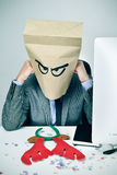 Man in his office with a paper bag in his head in christmas. A young caucasian businessman with a paper bag in his head with a sad face sitting at his office Royalty Free Stock Image