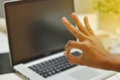 Man and okay finger with laptop background stock photos