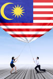 Man and his partner pulling down malaysian flag Stock Images