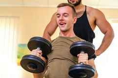 Man and his personal trainer exercising with dumbbells at the Gym. Technique exercises for the shoulders. novice athlete with coac. H Stock Photography