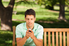 Man with his phone on the bench Stock Images