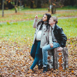 Man and his pregnant wife walks in the autumn park. Young married pregnant couple walking in the autumn park Royalty Free Stock Photos