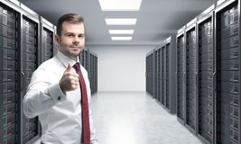 Man with his right thumb up in server room for data storage, pro Royalty Free Stock Images