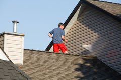 Man on his roof power washing the vinyl siding. A man standing on the roof of his house cleaning the siding with a power washer stock image