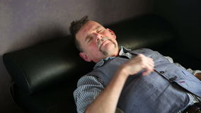 Man in his 50s lying on couch and resting stock video footage