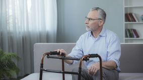 Man in his 60s sitting on sofa and looking at walking frame in front of him. Stock footage Stock Images