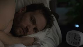 Man in his 40s suffering insomnia, turning in bed and looking angrily at clock. Stock footage stock footage