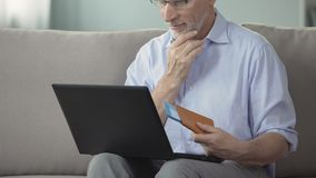 Man in his 60s viewing photos of resort town, booking hotel room on laptop. Stock footage stock footage