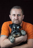 Man with his schnauzer puppy. Dog black and silver Royalty Free Stock Photos