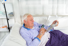 Man in his sickbed uses a credit card payment over the internet Royalty Free Stock Photo