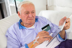 Man in his sickbed uses a credit card payment over the internet Stock Photography