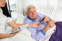Man in his sickbed uses a credit card payment over the internet Royalty Free Stock Photos