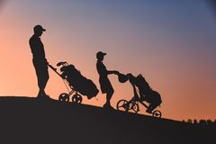 Man with his son golfers silhouette Royalty Free Stock Photo