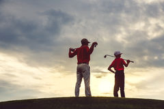 Man with his son golfers. Standing on golf course at sunset, back view Royalty Free Stock Photo