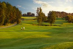 Man with his son golfers walking on golf course stock images