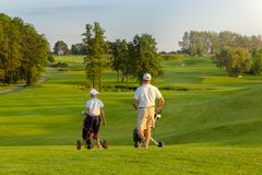 Man with his son golfers walking on golf course stock image