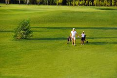 Man with his son golfers walking on golf course stock photo