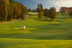 Man with his son golfers walking on golf course stock photography