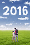 Man and his son looking at numbers 2016. Photo of a father standing at field with his son while looking at cloud shaped numbers 2016 Royalty Free Stock Images