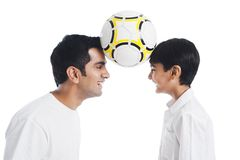 Man and his son playing with a soccer ball. And smiling Royalty Free Stock Photography