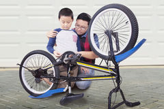 Man and his son repair a bicycle at home Royalty Free Stock Photo