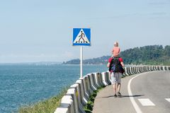 Man with his son on their shoulders walks along the highway against the background of the sea. Pedestrian crossing sign.  Stock Photography