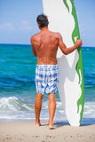 Man with his surfboard on the beach Stock Images
