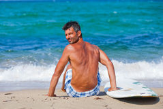 Man with his surfboard on the beach Royalty Free Stock Images