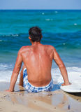 Man with his surfboard on the beach Stock Image