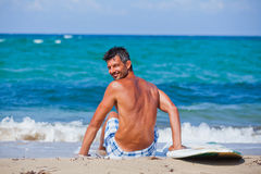 Man with his surfboard on the beach Royalty Free Stock Photos
