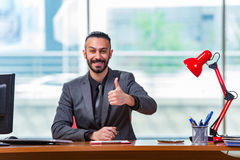 The man with his thumbs up in the office desk Stock Photos
