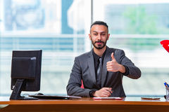 The man with his thumbs up in the office desk Royalty Free Stock Photos