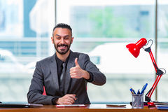 The man with his thumbs up in the office desk Stock Photography