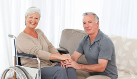 Man with his wife in a wheelchair. At home Stock Photography