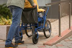 Man with his wife in wheelchair on ramp. Outdoors royalty free stock photo