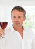 Man with his wineglass in his kitchen Royalty Free Stock Images