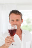Man with his wineglass in his kitchen Stock Image