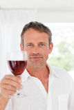 Man with his wineglass in his kitchen Stock Images